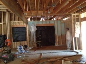 "Workers spraying 2"" of the foam on all exterior walls prior to installing the netting and blowing in the fiberglass insulation"