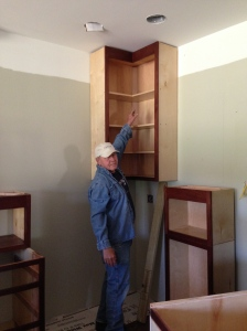 Bill reaching up to wall cabinet.