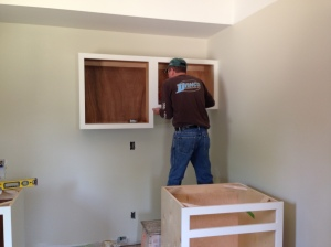 Laundry cabinets being installed